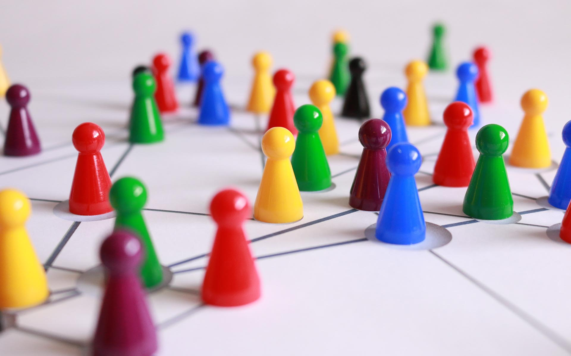 Picture of multicolored game pieces connected on a lined surface to accompany blog on International Networking Week.
